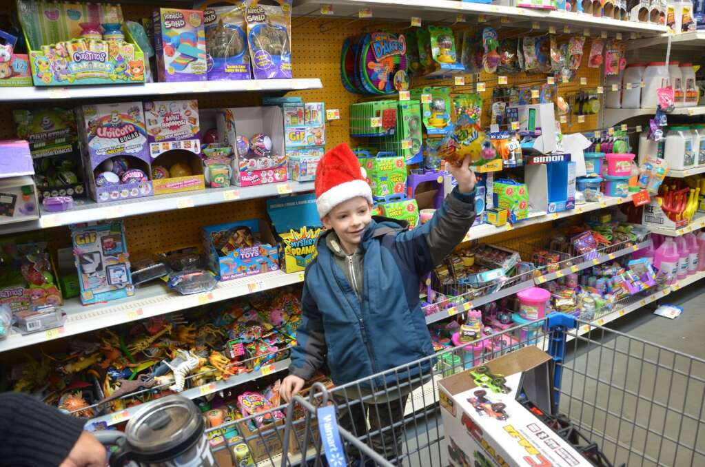 Mason tosses a toy into the cart