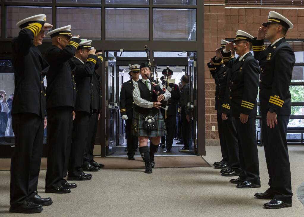 Firefighters stand at attention while a bagpiper leads the Hewitt family into the Eccles Center for a memorial service Thursday evening. Hundreds gathered to honor Paul Hewitt, the late Park City fire chief, who died July 23 in an off-duty accident. | (Tanzi Propst/Park Record)