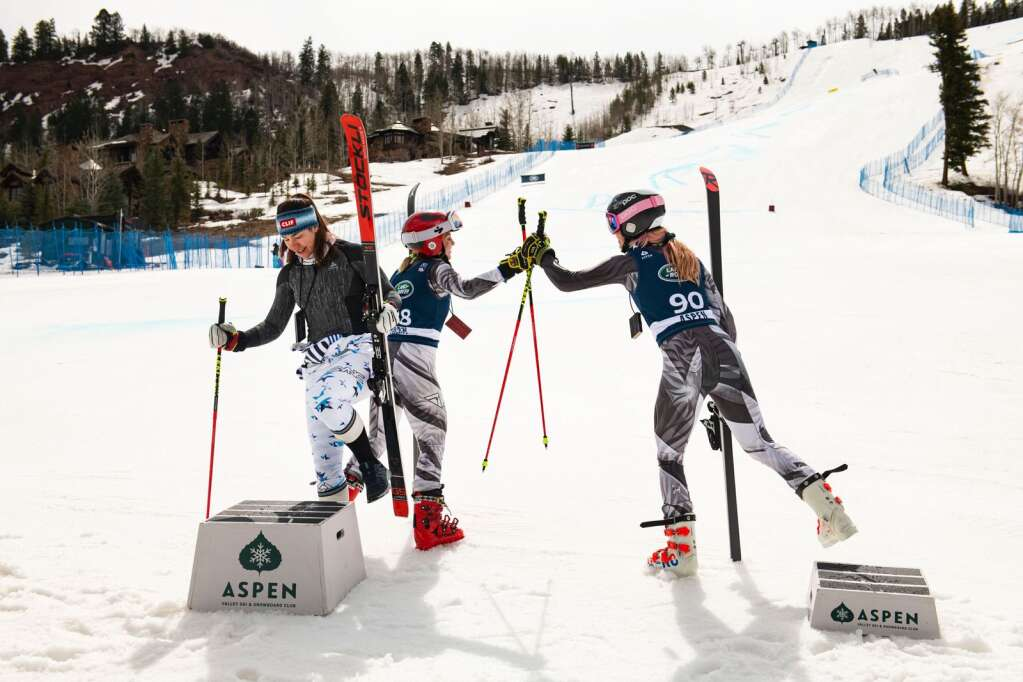 Alpine skier Lila Lapanja takes the first place podium as second and third place skiers Storm Klomhaus, center, and Tricia Mangan congratulate each other on the win from Women's Giant Slalom National Championships at the base of Aspen Highlands on Thursday, April 15, 2021. (Kelsey Brunner/The Aspen Times)