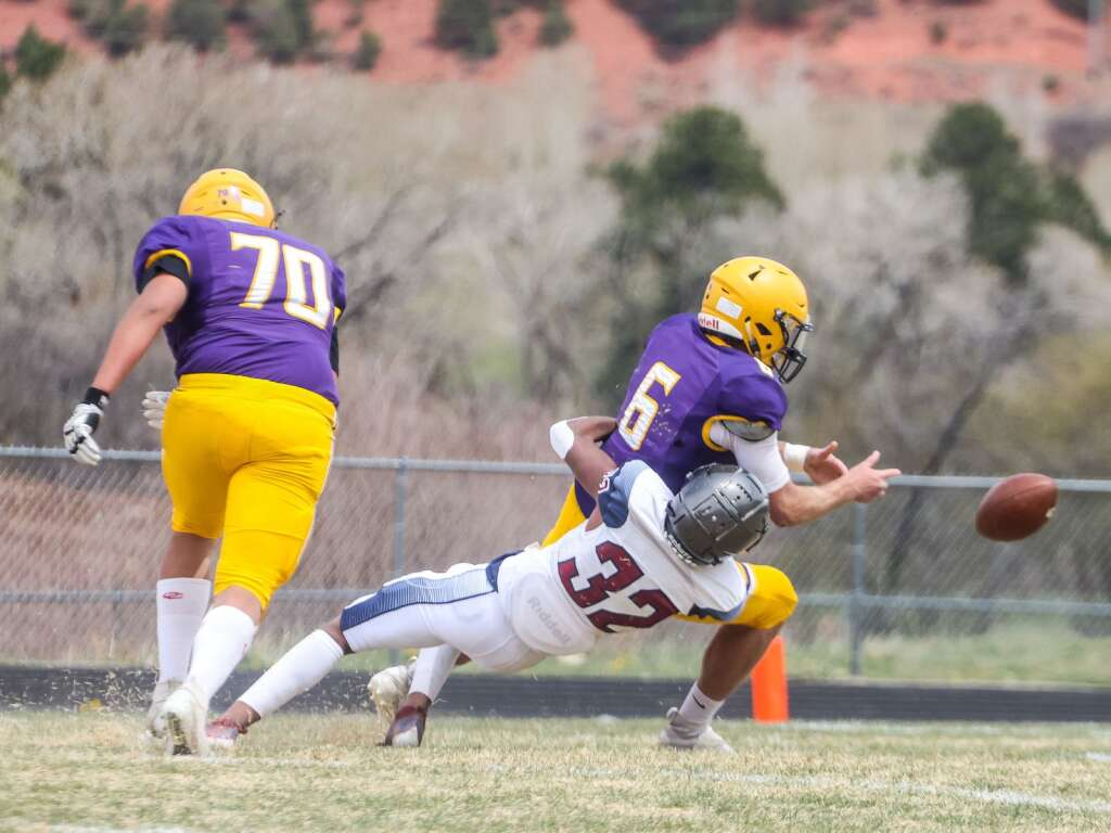 Basalt High School quarterback Matty Gillis has the ball knocked loose by Sand Creek's Keith Reddix in the Class 3A state quarterfinals on Saturday, May 1, 2021, in Basalt. The Scorpions won, 27-22. Photo by Austin Colbert/The Aspen Times.