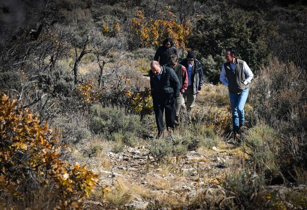 Colorado Gov. Jared Polis and political leaders head up the hill overlooking Sweetwater Lake for Wednesday afternoon's press conference. |Chelsea Self/Post Independent