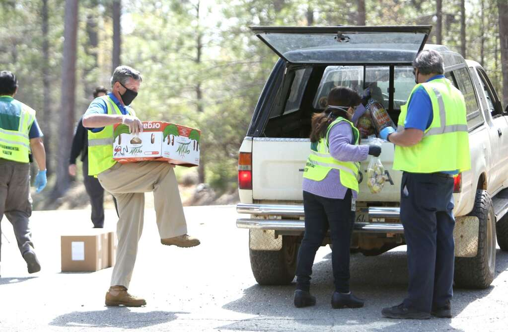 Nevada County Disaster Service Workers help load up a vehicle with food Thursday afternoon at the Grizzly Hill School drive-thru distribution site on the San Juan Ridge. | Photo: Elias Funez
