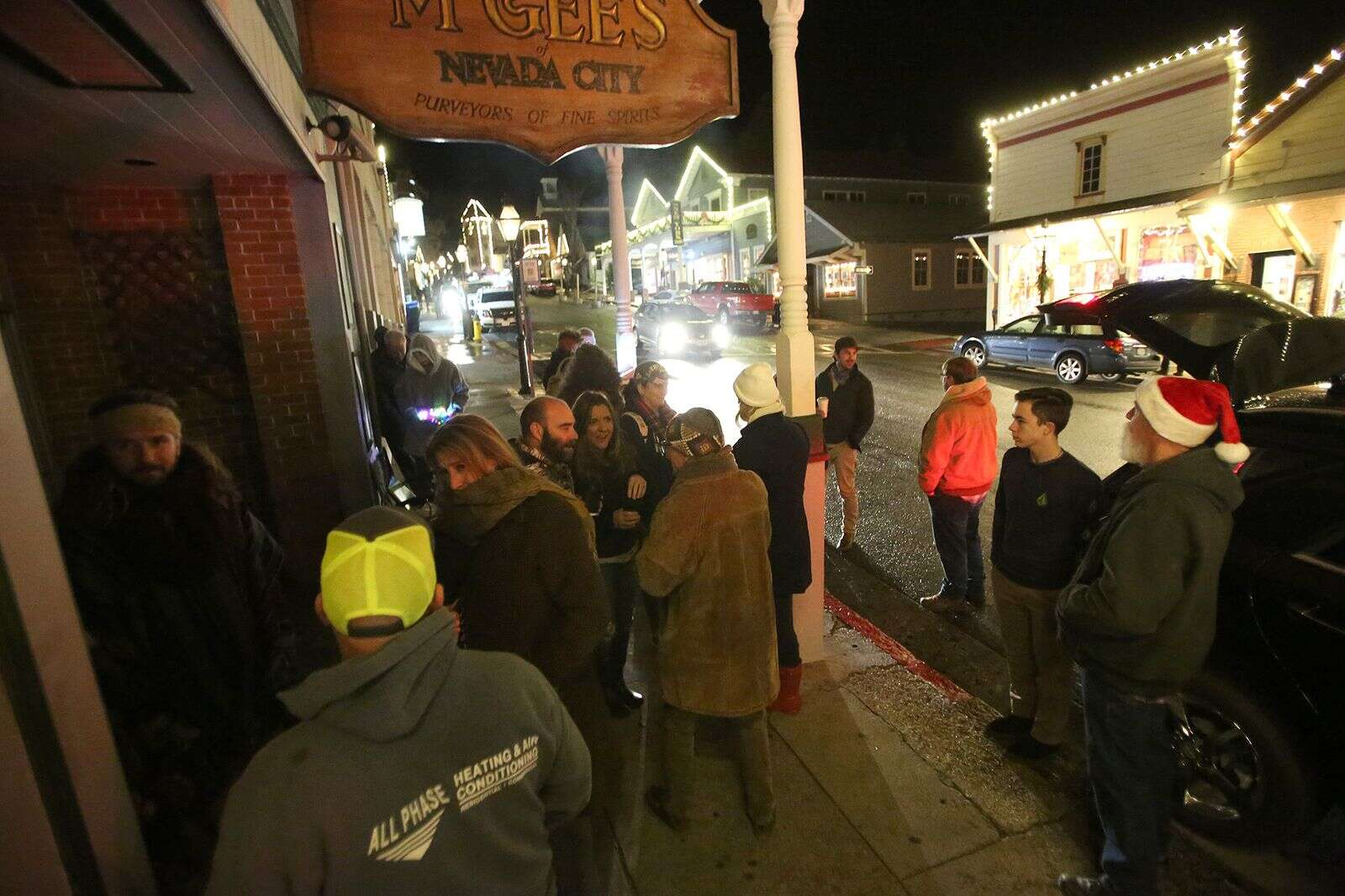 People gather under the awning in front of McGee's in Nevada City, where a few dozen attendees to the Nevada City Revival gathered to protest the regional stay at home orders.   Elias Funez