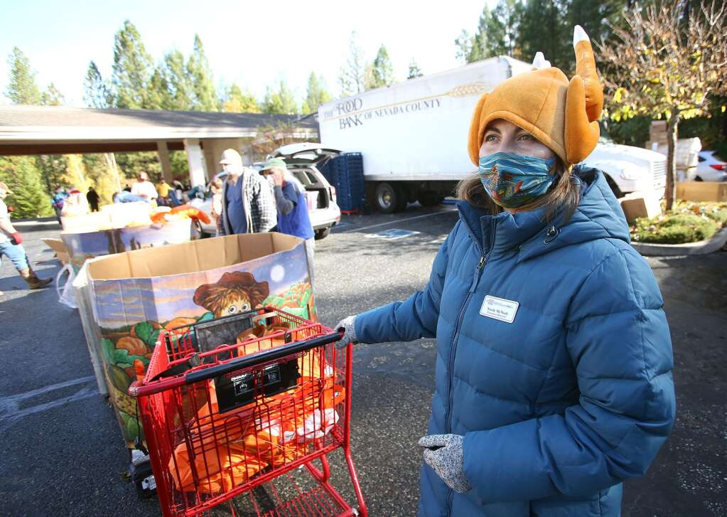 Food Bank of Nevada County Executive Director Nicole McNeely dons a festive hat while helping to fill vehicles with food for the Thanksgiving holiday during Thursday's weekly drive-thru distribution at Grass Valley Seventh Day Adventist Church. About 1,200 families were served Nov. 19 according to McNeely. | Photo: Elias Funez