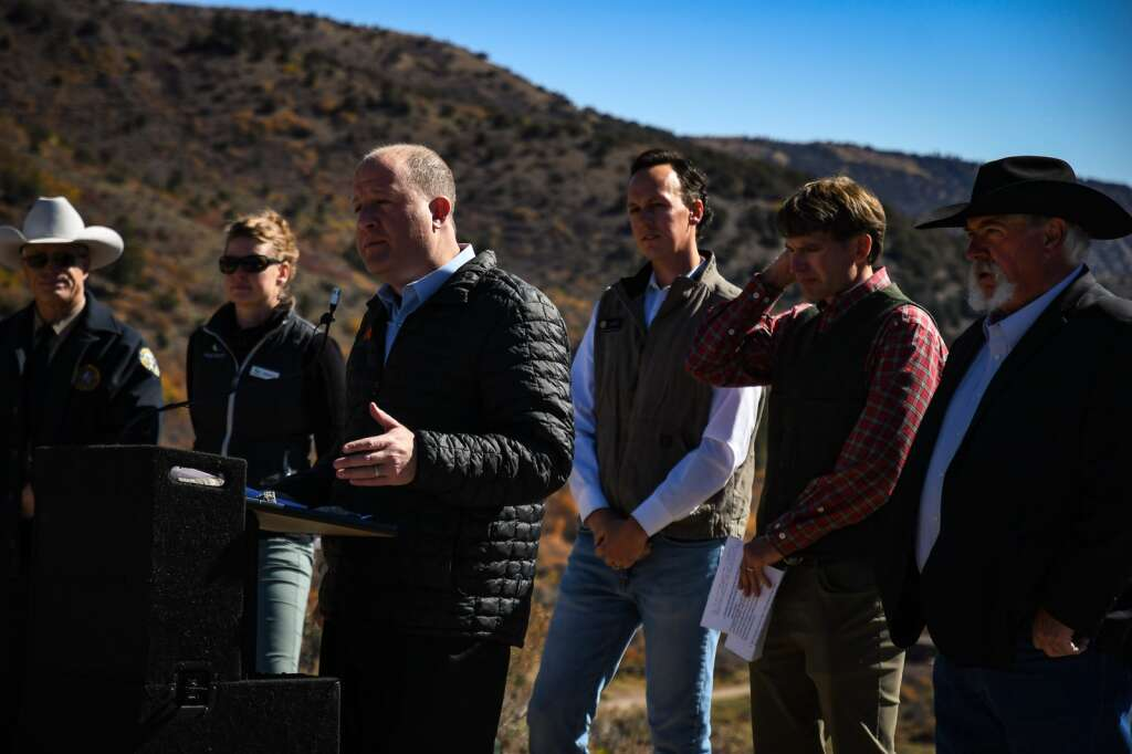 Colorado Gov. Jared Polis and other political leaders stand in front of the audience and members of the press during a press conference at Sweetwater Lake on Wednesday. |Chelsea Self/Post Independent