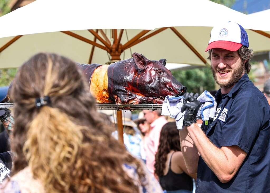 Aspens Home Team BBQ carries a pig through the crowd that will eventually be eaten at Snowmass Base Village during the Heritage Fire on Saturday, July 31, 2021.  Photo by Austin Colbert / The Aspen Times.