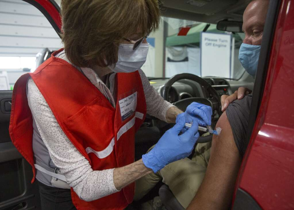 Gail Teasley administers a Moderna vaccine to a patient at the drive-thru COVID-19 vaccination clinic at the Utah Film Studios. | Tanzi Propst/Park Record