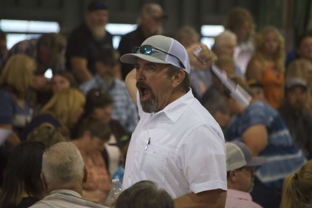 Auctioneer's assistants alert the auctioneer to a new bid from their section at the Moffat County Fair livestock auction Saturday evening. | Cuyler Meade / Craig Press
