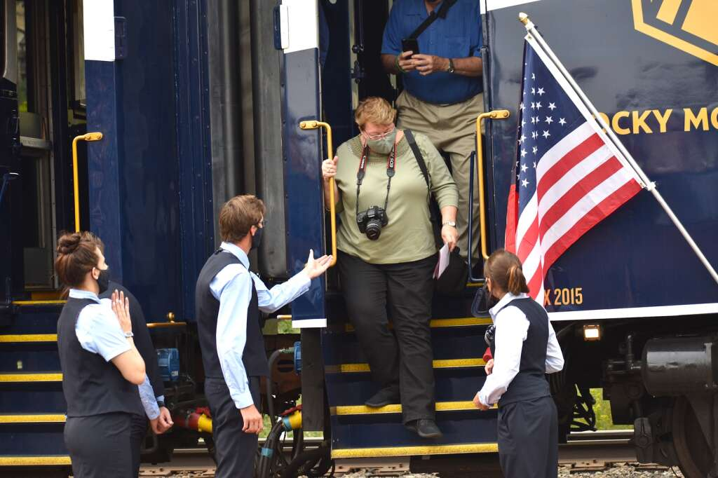 Train crews assist a Rocky Mountaineer passenger off the train during the maiden Rockies to the Red Rocks stop in Glenwood Springs on Sunday, Aug. 15, 2021.