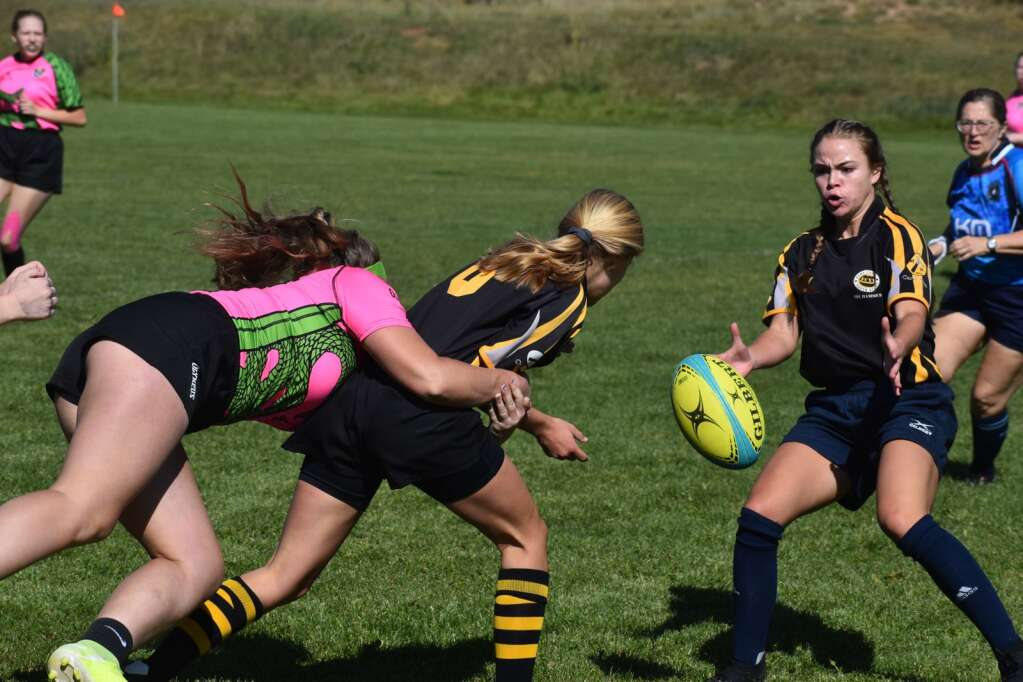 A Highlands Ranch Viper tackles a Ft. Collins Hammer as she tosses the ball to a teammate during a rugby game at Colorado Mountain College, Spring Valley campus on Saturday.  Ray K. Erku / Post Independent