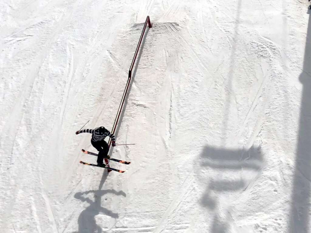 A skier slides along a rail in the Coney Glade terrain park during closing day at Snowmass on Sunday, April 25, 2021. (Kaya Williams/The Aspen Times)