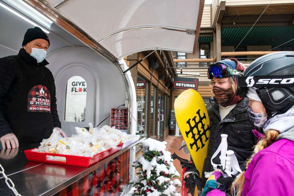 Snowmass Guest Services Bob Post, left, hands out slices of King Cake to people a the s'mores cart in the Snowmass Mall during Mardi Gras on Tuesday, Feb. 16, 2021. (Kelsey Brunner/The Aspen Times)