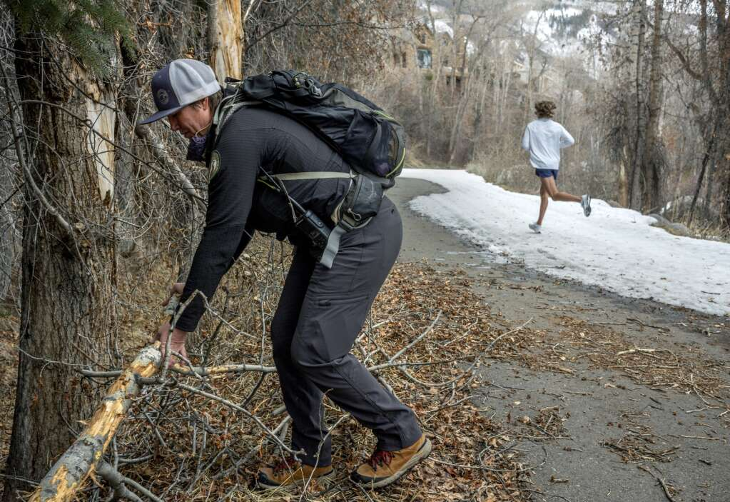 Pitkin County Open Space and Trails ranger Megan Ballard at right removes debris from the Rio Grande trail in Aspen recently. (Daniel Bayer/Aspen Journalism)