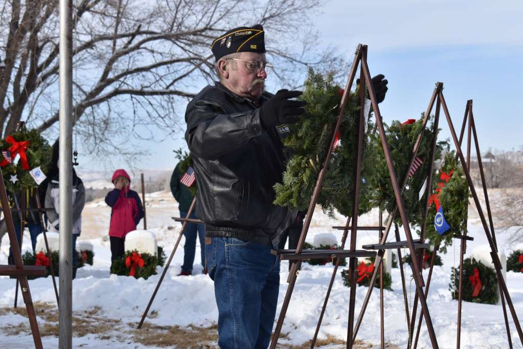 Ed Wilkinson, a U.S. Army veteran, places a wreath for the Merchant Marines Saturday.