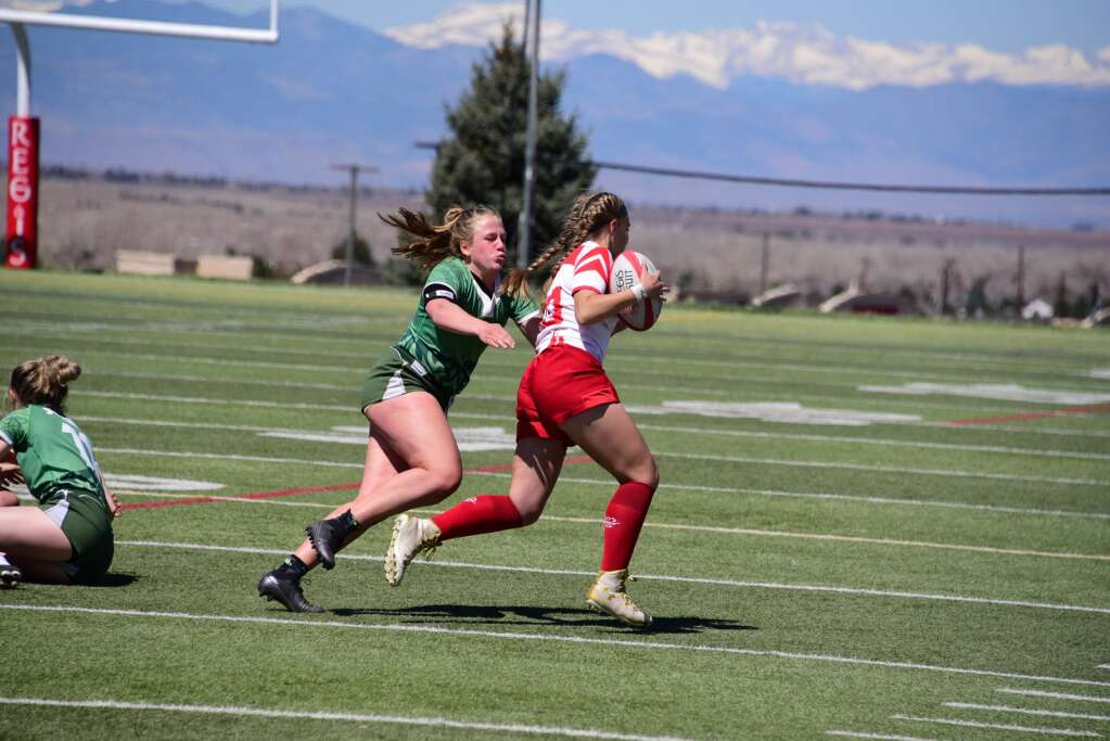 Summit's Millie Carleton attempts to tackle Regis Jesuit's Patricia Terry during the Tigers' three victories Saturday at Regis Jesuit High School in Aurora. | Photo by Jimmy Terry
