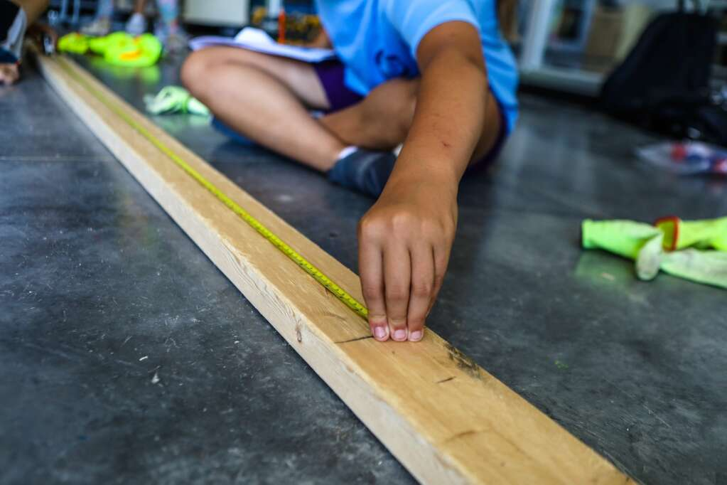 Kids took turns doing different steps of construction cornhole boards during YouthPower365's Pathfinders Camp build day Friday at Eagle Valley Elementary School in Eagle.  | Chris Dillmann/cdillmann@vaildaily.com
