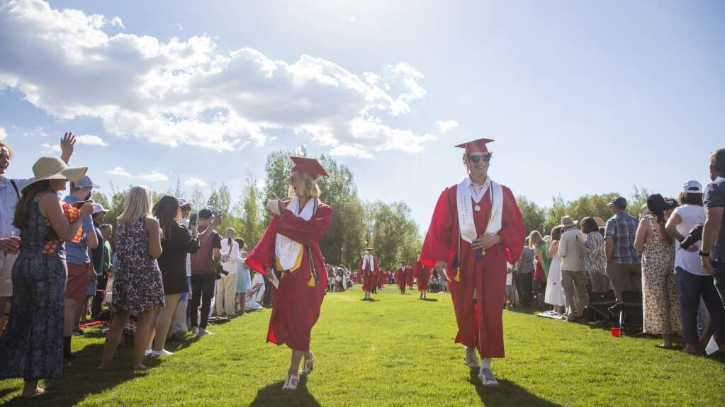 Senior Class President Meghan Buchholz, left, waves to a friend as she and Student Body President Cooper Strophe begin the procession of the senior class on the North 40 playing fields during the class of 2021's commencement ceremony Thursday evening, June 3, 2021. Both Buchholz and Strophe spoke to their fellow classmates and attendees during the ceremony. (Tanzi Propst/Park Record)