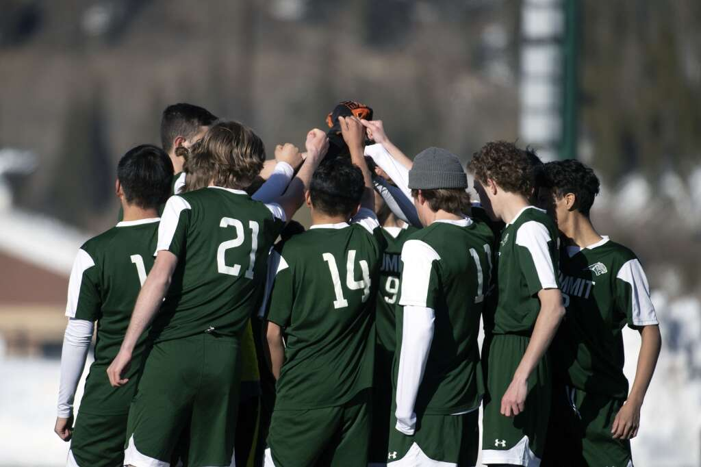 Summit High School boys varsity soccer players raise their fists together before the start of the second half of their home opener against the Steamboat Springs High Sailors at Climax Molybdenum Field at Tiger Stadium on Thursday, March 18, 2021. The Tigers lost to the Sailors 3-0. | Photo by Jason Connolly / Jason Connolly Photography