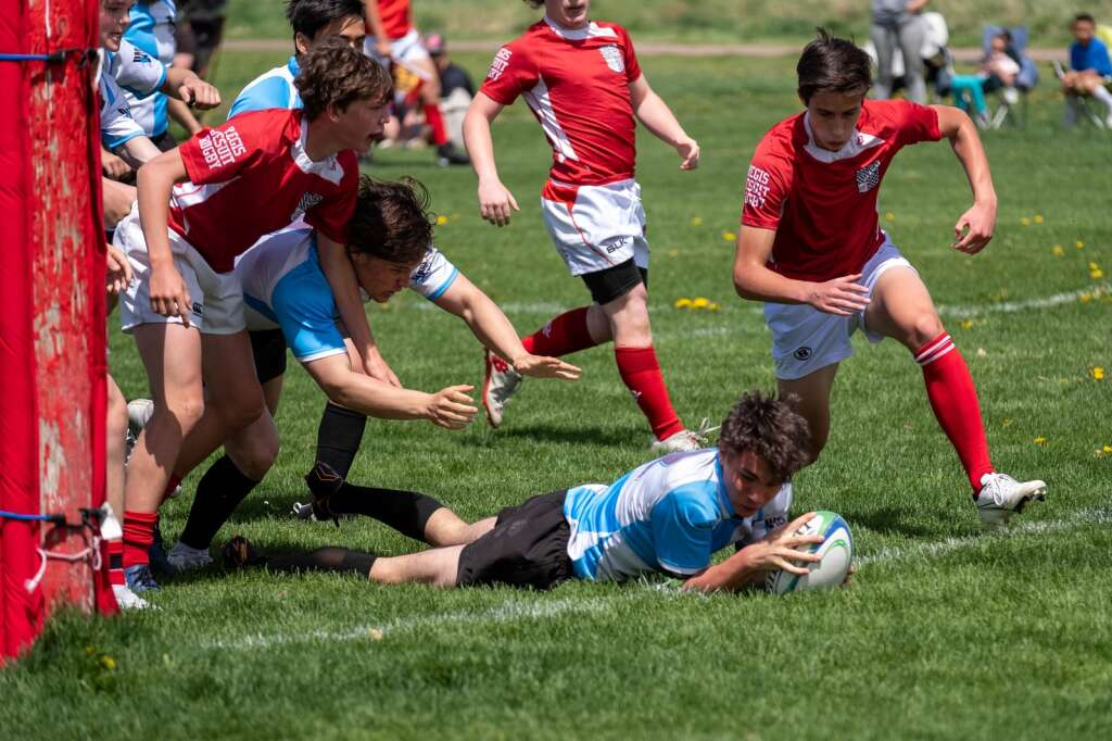 Jack Hodge carries the ball during the Summit High School boys rugby game versus Regis Jesuit at Cook Park in Denver on Saturday, May 8.   Photo by Stefan de Vogel
