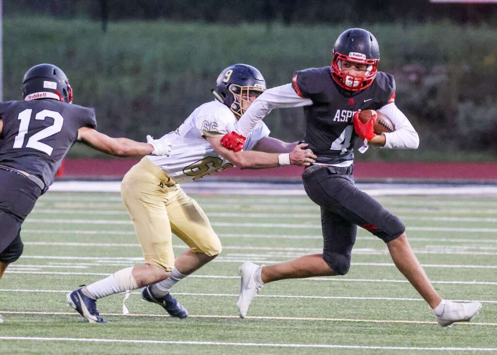 Aspen High School's Brady Haisfield, right, fends off tacklers as the football team hosts Colorado Springs Christian on Friday, Aug. 27, 2021, on the AHS turf. | Photo by Austin Colbert/The Aspen Times