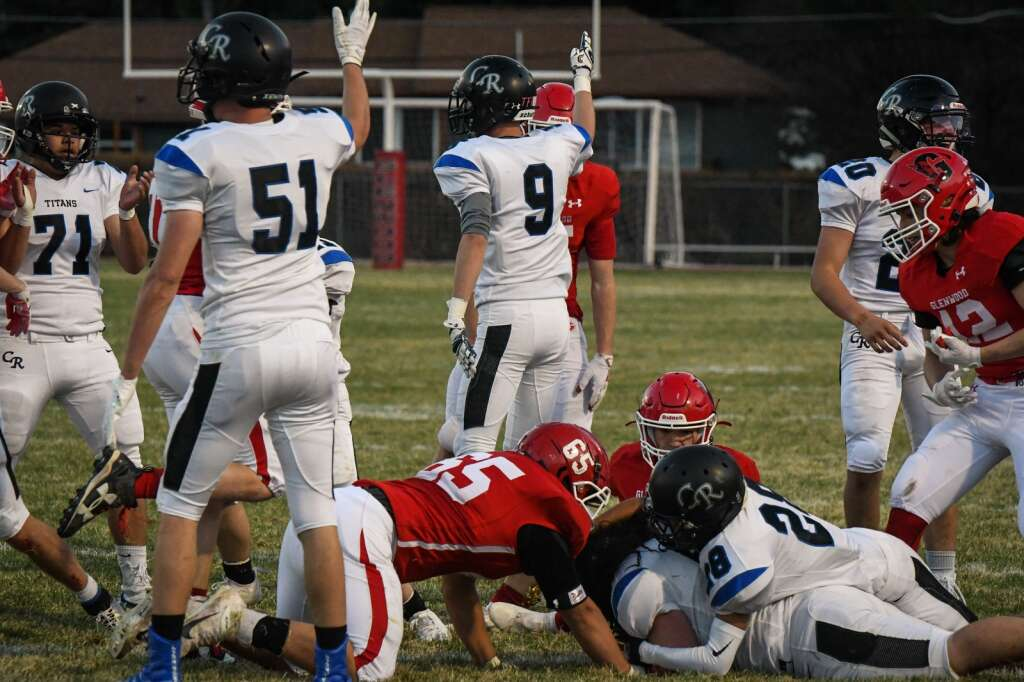The Coal Ridge Titans signal they have possession of the ball after it was fumnbled by the Glenwood Springs Demons during Friday night's game. |Chelsea Self / Post Independent