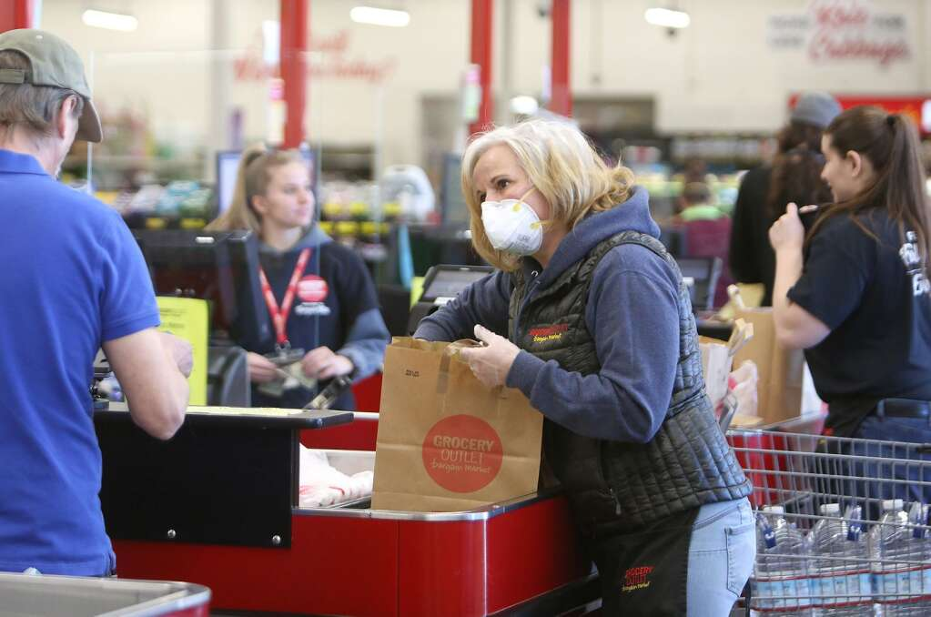 Front lead at Grocery Outlet Kasandra Berry, wears an N95 mask while helping to bag groceries early April in Grass Valley. While face coverings weren't required early on in the pandemic in the U.S., folks began voluntarily wearing them after noting mask wearing countries were fighting the coronavirus better. | Photo: Elias Funez