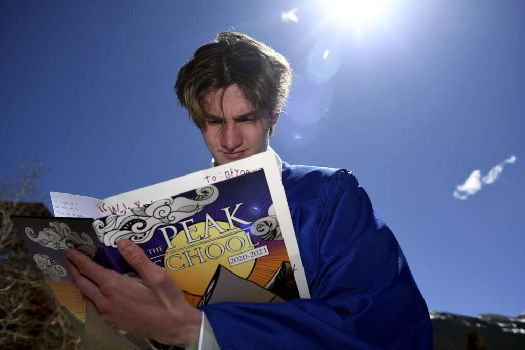 Tucker Neal, graduate of The Peak School, signs a yearbook after the graduation ceremony at Copper Mountain Resort on Thursday, May 27.   Photo by Jason Connolly /Jason Connolly Photography