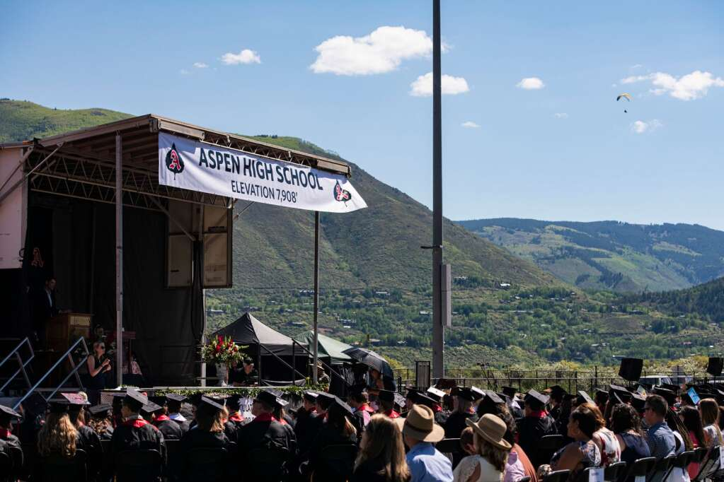 A paraglider prepares to land at Marolt Open Space but can be seen from the Aspen High School graduation ceremony on the turf field on Saturday, June 5, 2021. (Kelsey Brunner/The Aspen Times)