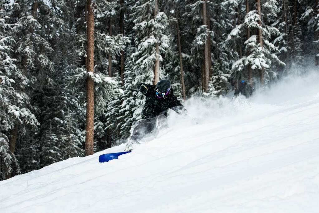 A snowboarder rides through powder on the opening day of Aspen Highlands for the 2020-21 season on Friday, Dec. 18, 2020. (Kelsey Brunner/The Aspen Times)