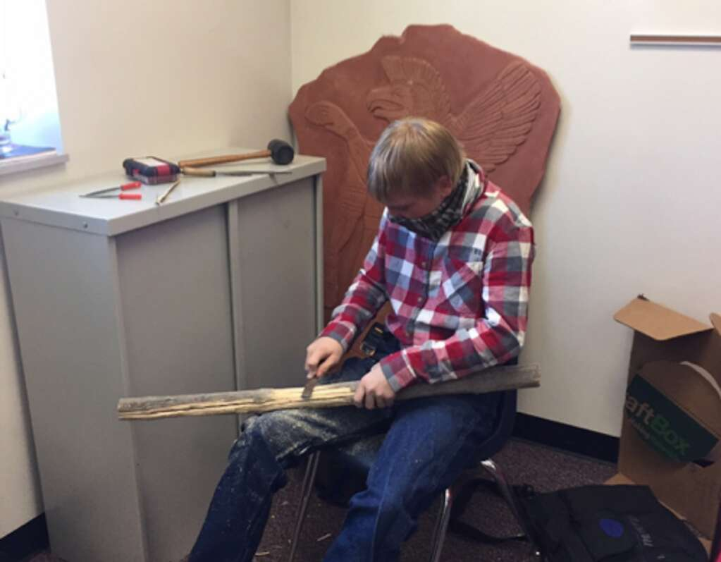 Alex Burke carving an atlatl spear thrower out of a stick.