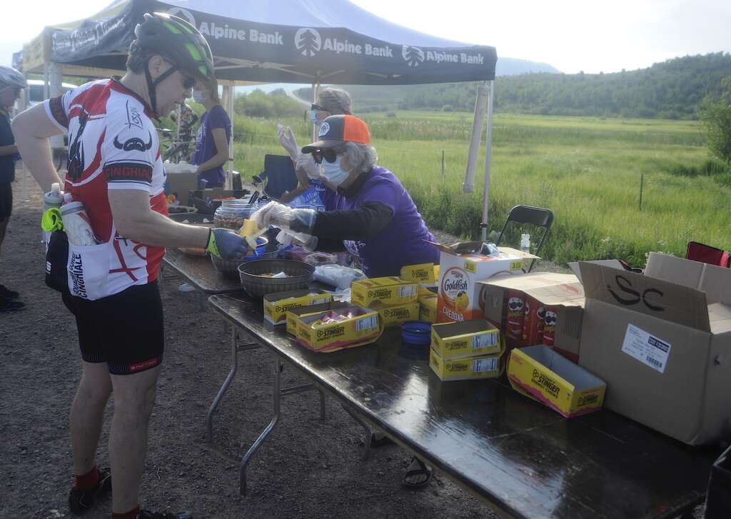Mary Huber hands out food to cyclists at the Stagecoach aid station as part of the Tour de Steamboat Springs on Saturday. (Photo by Shelby Reardon)