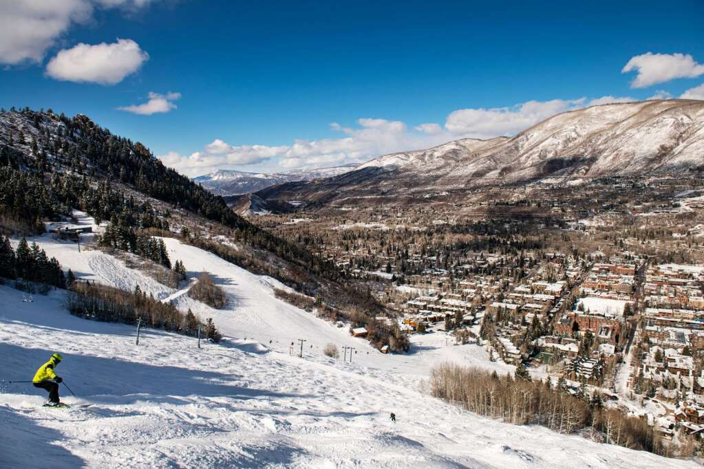 A skier drops off of a catwalk into a mogul run with view of Lift 1A and the town of Aspen on Thursday, Feb. 18, 2021. (Kelsey Brunner/The Aspen Times)