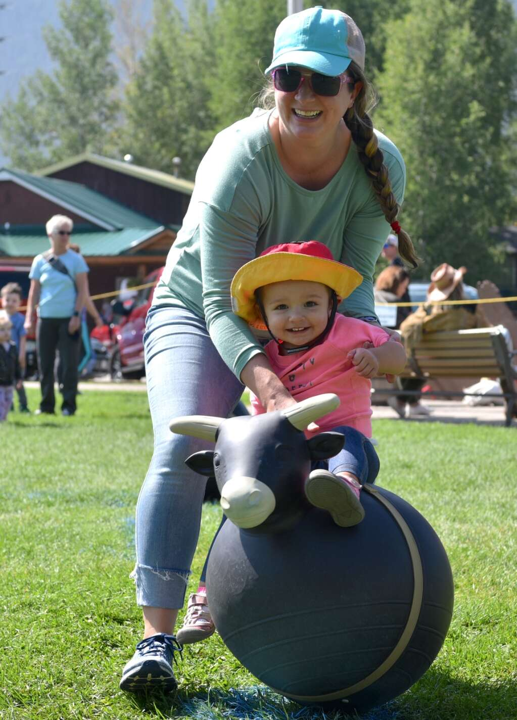 A mom helps her daughter ride a bull as part of festivities for Buffalo Days on Saturday in Grand Lake.   Amy Golden / agolden@skyhinews.com