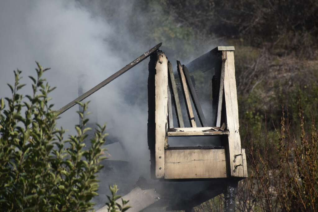 An wooden exterior staircase smolders after being sprayed with water. |Ray K. Erku / Post Independent
