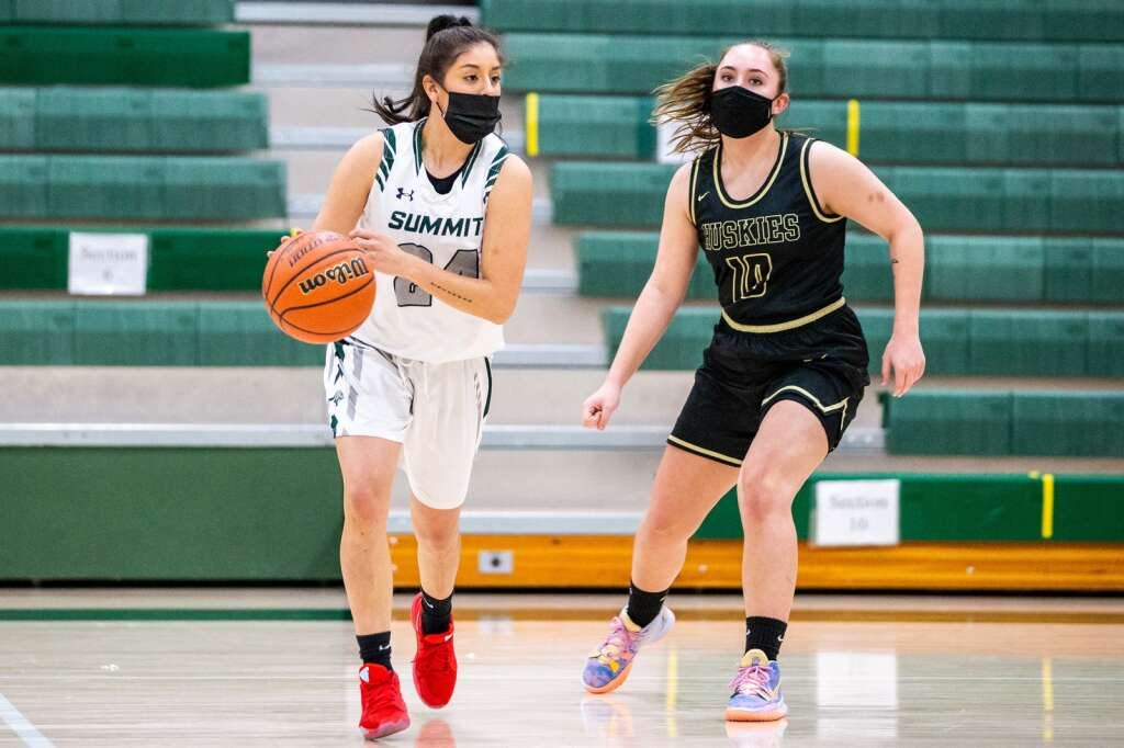 Summit's Karen Barrios dribbles the ball past Battle Mountain's Jade Harding during the girls varsity game on Thursday, Feb. 25, at Summit High School in Breckenridge. The Tigers fell to the Huskies, 70-34. | Photo by Liz Copan / Studio Copan