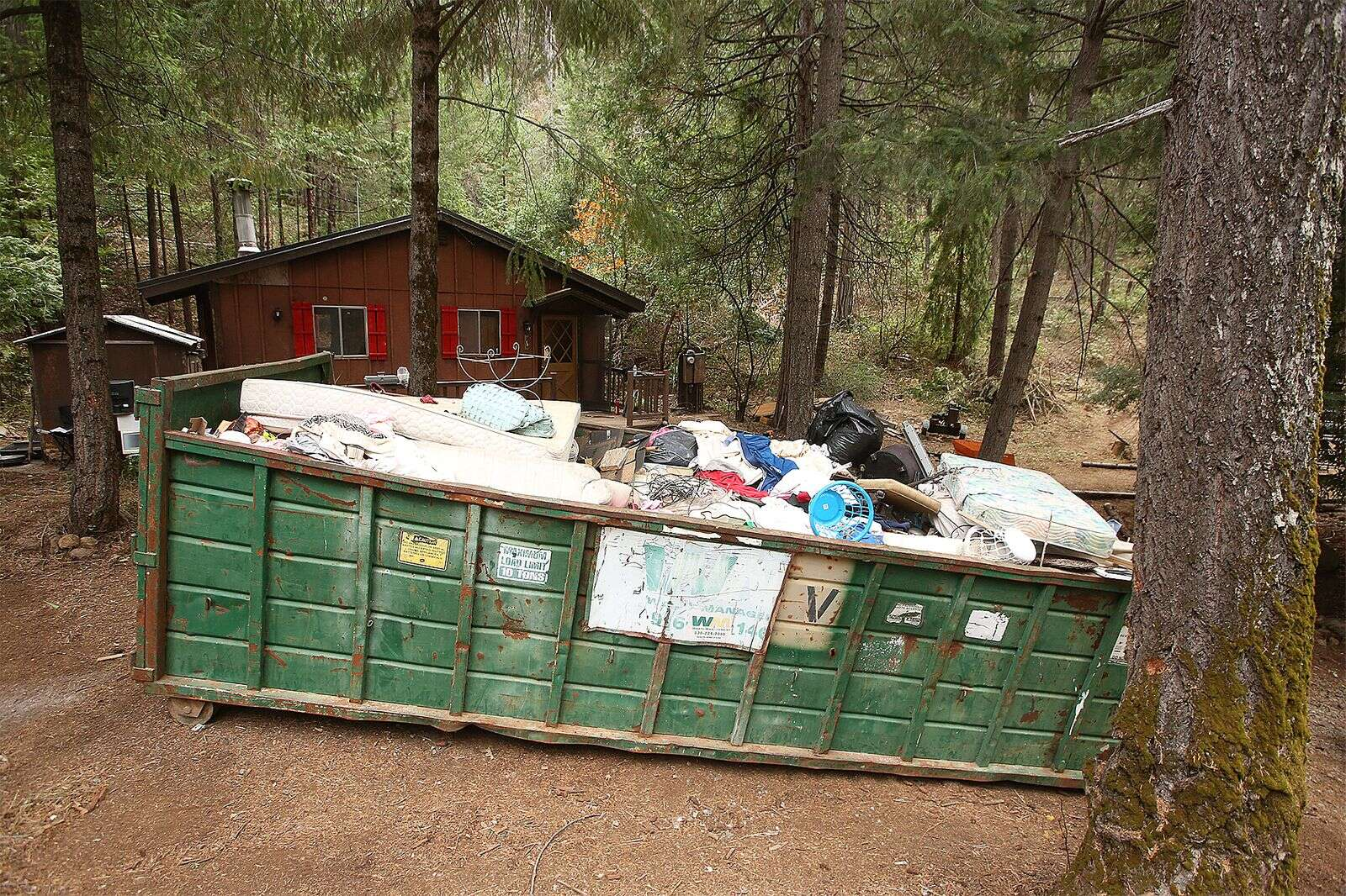 A large trash dumpster awaits to be hauled to the landfill after being filled with refuse left on the Marlowe's rural Nevada City property by a band of squatters. One of those, Amanda Carlson, has a January court date and remains in custody.   Photo: Elias Funez