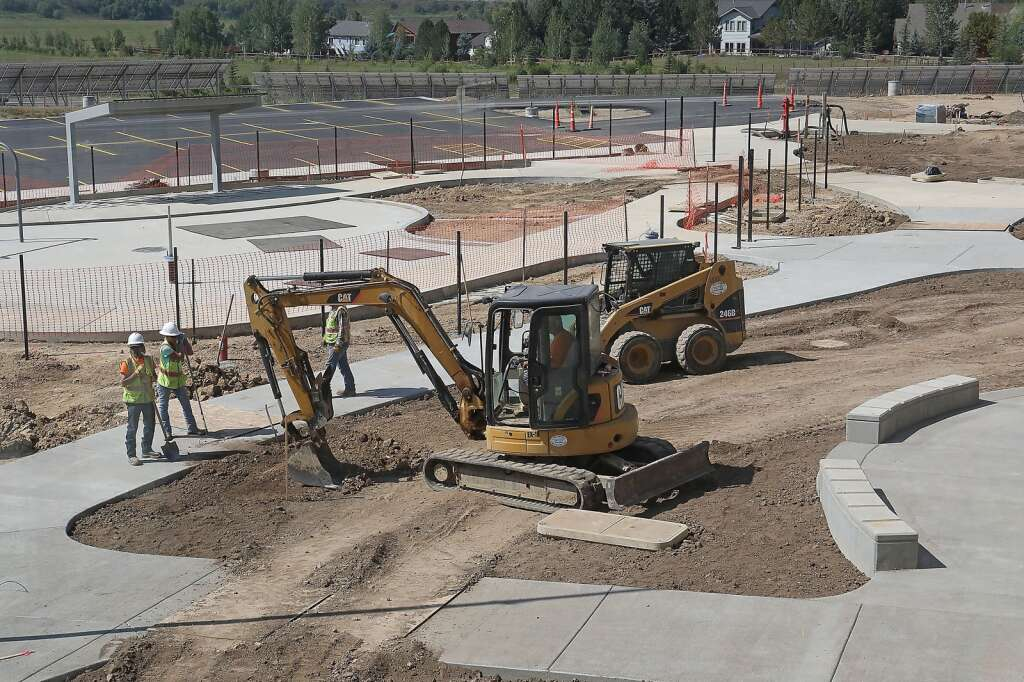 Crews work on the walkways and concrete on the outside of the new Sleeping Giant School. (Photo by John F. Russell)