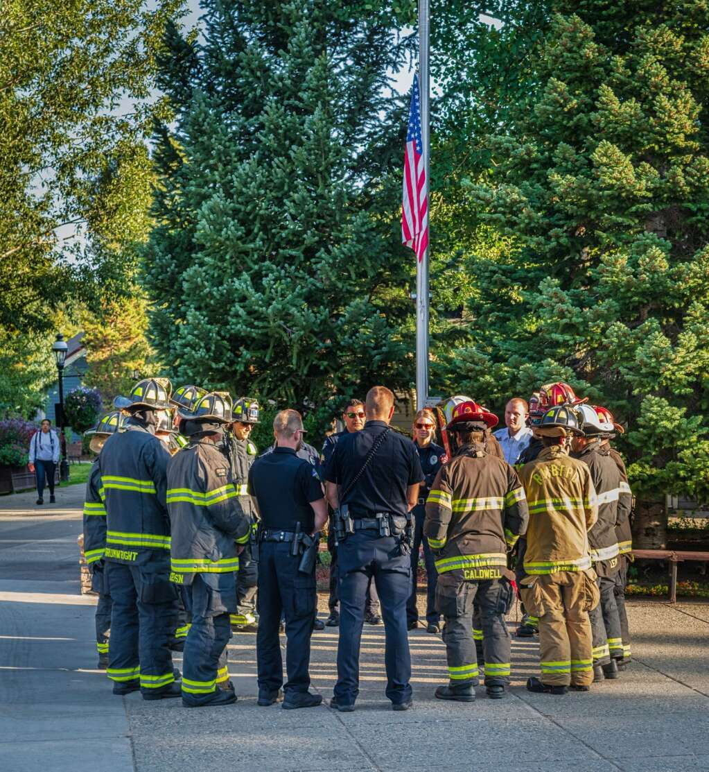 Firefighters from the Red, White & Blue Fire Protection District, as well as officers from the Breckenridge Police Department, gather in a circle to watch the flag be raised at half-staff on the Blue River Plaza on Sept. 11, 2021. The organizations hosted a small, brief ceremony to honor the 20th anniversary of 9/11.   Joel Wexler/For the Summit Daily News