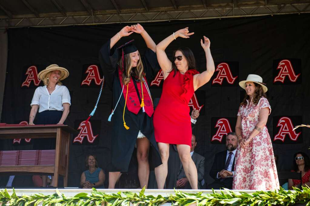 Aspen High School graduate Emily Kinney, left, and her mom Erin Kinney perform the signature dance from the movie 'Parent Trap' after Erin gave her daughter her diploma on stage of the 2021 commencement ceremony on the football field on Saturday, June 5, 2021. (Kelsey Brunner/The Aspen Times)