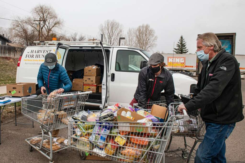 Matt Hooks, left, and Gray Warr unload grocery carts with food for Harvest for Hunger delivered from the El Jebel City Market by operations receiving manager Keith Sandquist on Tuesday, March 23, 2021. (Kelsey Brunner/The Aspen Times)