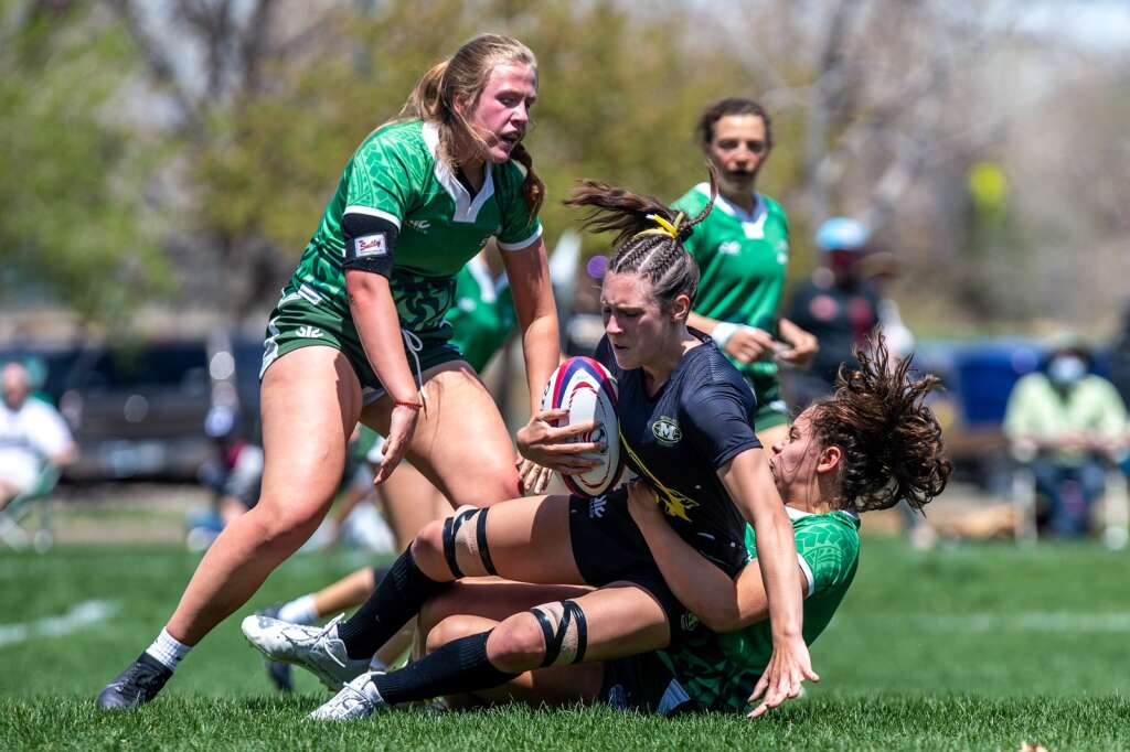 Bryton Ferrari, right, and Millie Carleton tackle a Monarch player while teammate Jenna Sheldon observes during Summit High School's state championship games versus Monarch High School at Cook Park in Denver on Saturday, May 1, 2021. | Photo by Liz Copan / Studio Copan