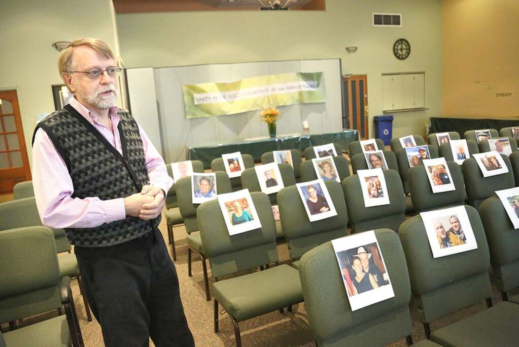 Unity in the Gold Country Spiritual Center's Reverend Jerry Farrell stands among pictures of his congregation, placed on the seats of the Cambridge Court center Thursday afternoon. Farrell is utilizing Zoom and FaceTime to connect with folks and will be utilizing the sanctuary for a wall of remembrance to help those grieving their loved ones during this time. | Photo: Elias Funez
