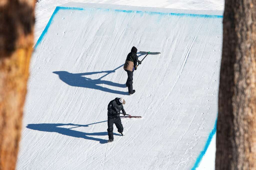 Long shadows grow in the early afternoon light as groomers perfect the first jump on the slopestyle course during the 2021 X Games Aspen on Sunday, Jan. 31, 2021. (Kelsey Brunner/The Aspen Times)