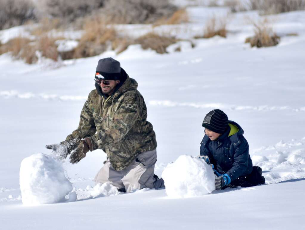 A father and son take a break from ice fishing to build a snowman. | Amy Golden / agolden@skyhinews.com