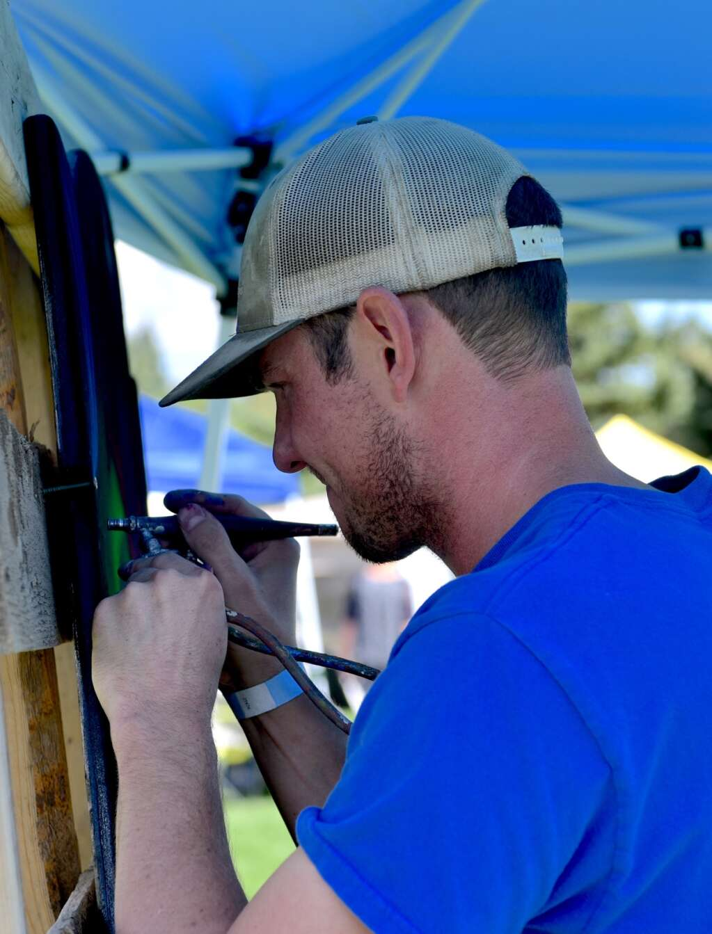 Andrew Midthun airbrushes his piece for Art in the Park on Saturday, Sept. 3, 2021, at Polhamus Park in Granby.   Amy Golden/Sky-Hi News