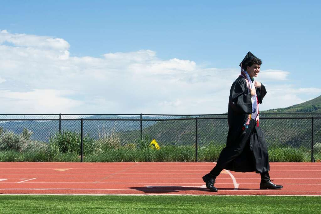 Aspen High School's graduate Jeremy Martin walks along the track around the turf field before the commencement ceremony at the school on Saturday, June 5, 2021. (Kelsey Brunner/The Aspen Times)