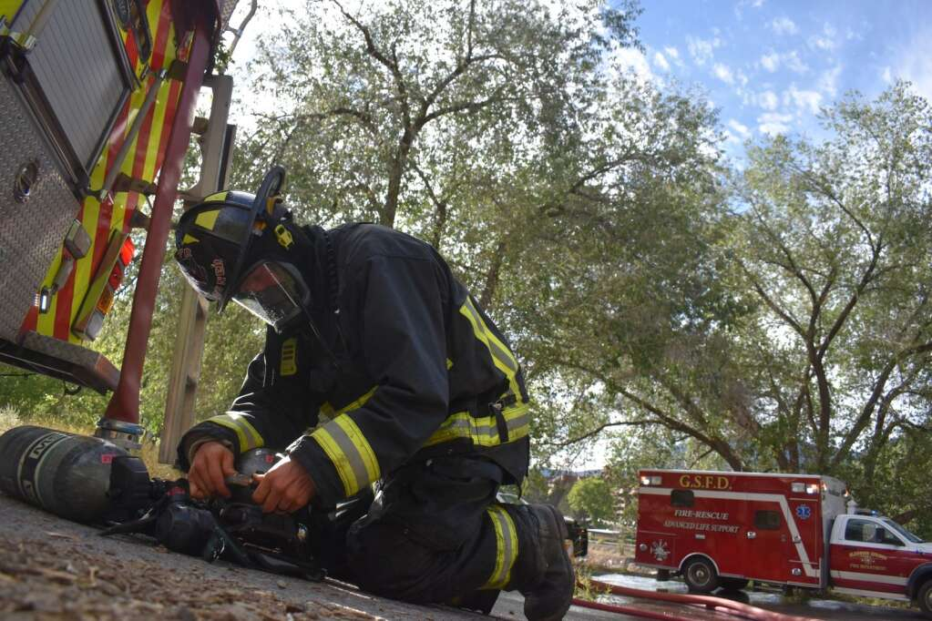 A firefighter switches oxygen tanks during a house fire in Glenwood Springs on Saturday. |Ray K. Erku / Post Independent
