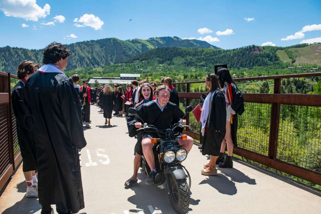 Aspen High School graduate John Doyle drives his scooter over the Tiehack Bridge with fellow graduate Jamison Delaney on the back after the 2021 commencement ceremony in Aspen on Saturday, June 5, 2021. (Kelsey Brunner/The Aspen Times)