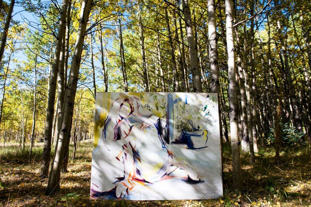 A painting by Denver-based artist Kaitlyn Tucek is displayed between two trees in an aspen grove in the Ashcroft Ghost Town outside of Aspen as part of her two-day exhibition 'The Lilac Hour' outside of Aspen on Friday, Sept. 17, 2021. (Kelsey Brunner/The Aspen Times)