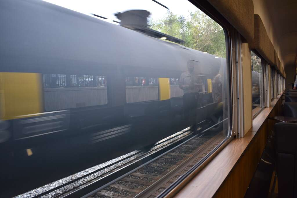 A freight train passes on the other tracks, as seen from inside the lounge car of the Rocky Mountaineer as it sat in downtown Glenwood Springs Sunday evening.